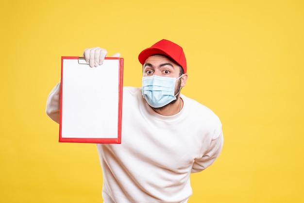 Курьер-мужчина в маске держит заметку на желтом