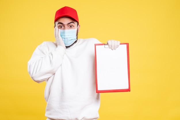黄色のファイル ノートを保持しているマスクの男性宅配便