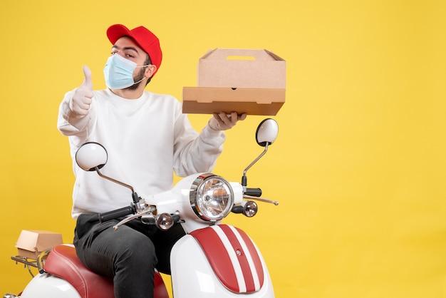 Мужской курьер в маске держит коробку с едой на желтом