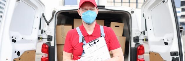 보호 의료 마스크를 쓴 남성 택배가 소포를 배달합니다.