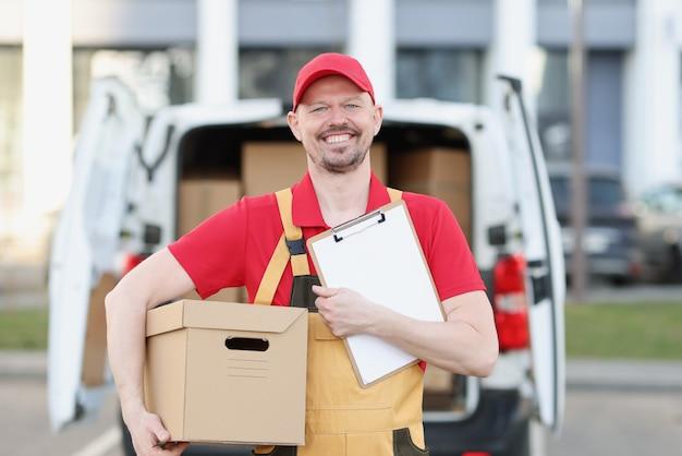 制服を着た男性の宅配便は、ボックスとトラックの背景にクリップボードと段ボール箱を保持します。
