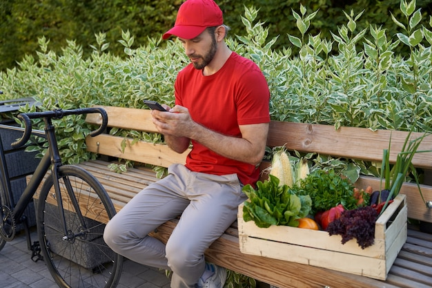 屋外のベンチに座って使用している制服を着た男性の宅配便