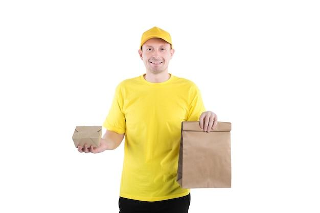 격리 된 흰색 배경에 고객에게 공예 포장에서 음식 주문을 제공하는 노란색 제복을 입은 남성 택배.