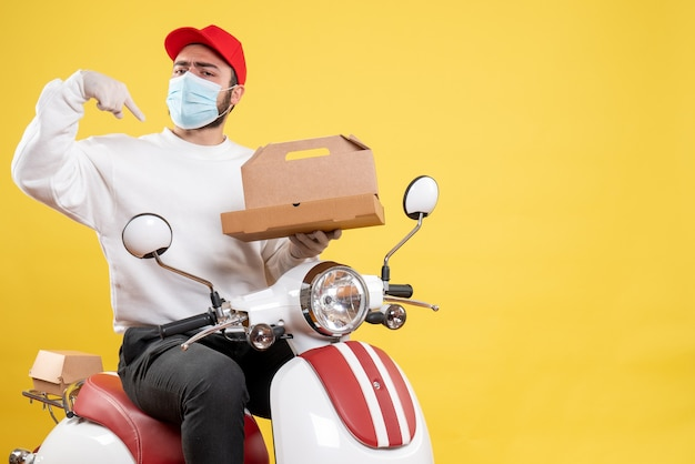 Male courier in mask on bike holding food box on yellow