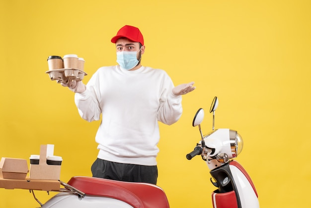 Male courier in mask holding coffee on the yellow