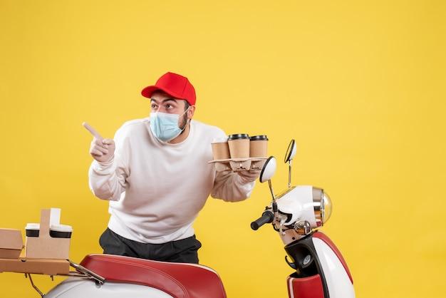 Corriere maschio in maschera con caffè su giallo