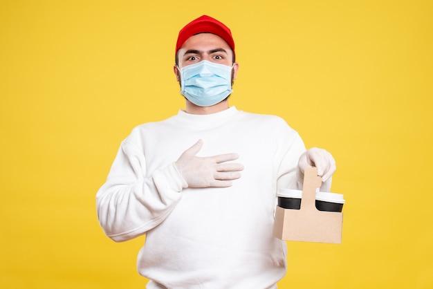 Corriere maschio in maschera che tiene il caffè di consegna su giallo chiaro