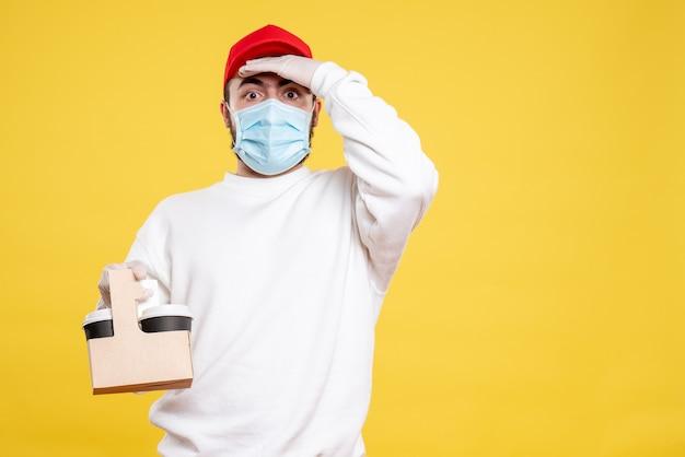 Corriere maschio in maschera che tiene il caffè di consegna su giallo