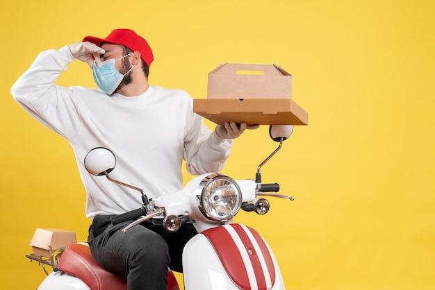 Corriere maschio in maschera che tiene cibo per la consegna chiudendo il naso sul giallo