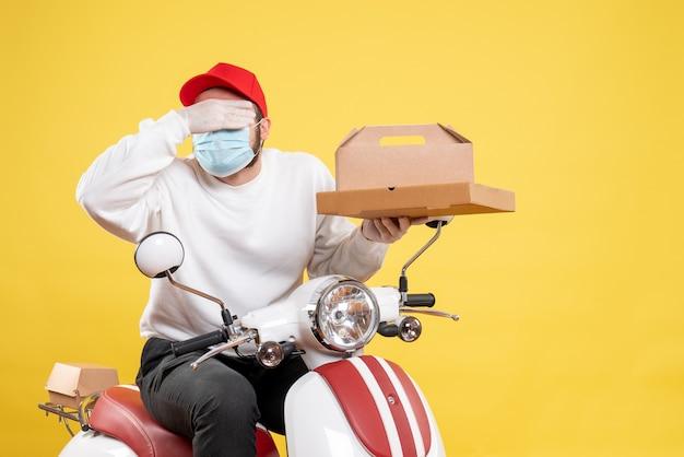 Corriere maschio in maschera che tiene cibo per la consegna su giallo