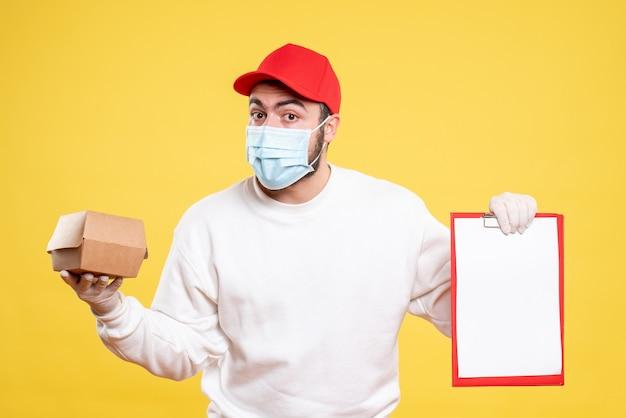 Corriere maschio in maschera con nota di file e piccolo pacchetto di cibo su giallo