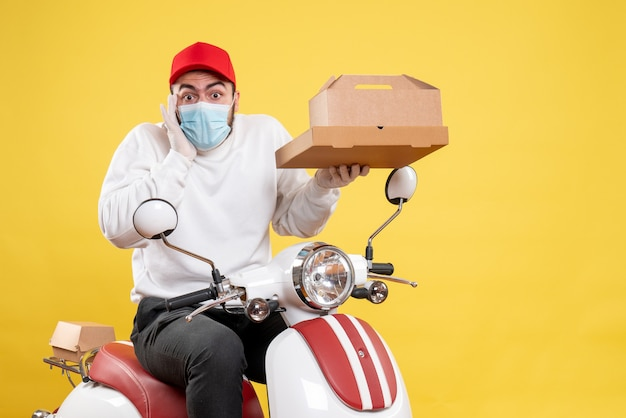 Male courier in mask holding food box on yellow