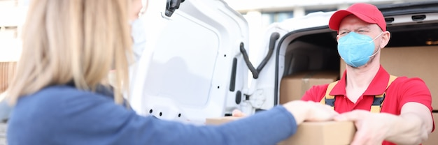 Курьер-мужчина в защитной медицинской маске дает женщине картонную коробку