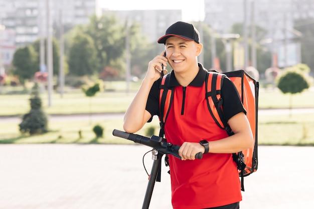 等温フードケースボックス付きの男性宅配便が家の入り口に到着し、クライアントを呼びます