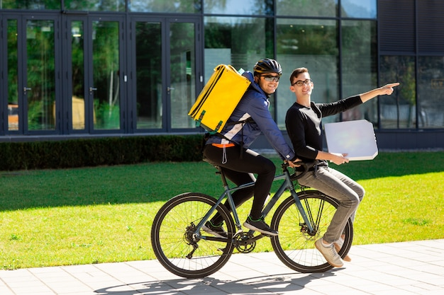 Male courier with thermal bag is carrying a guy with a box on a bicycle trunk.