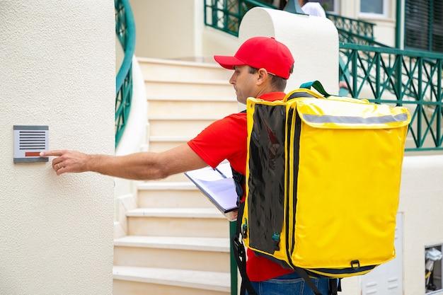 열 가방 및 클립 보드 울리는 초인종을 가진 남성 택배. 빨간 제복을 입은 심각한 배달원, 도어 벨을 밀고 야외에서 서서 주문 택배 서비스 및 게시물 개념 제공