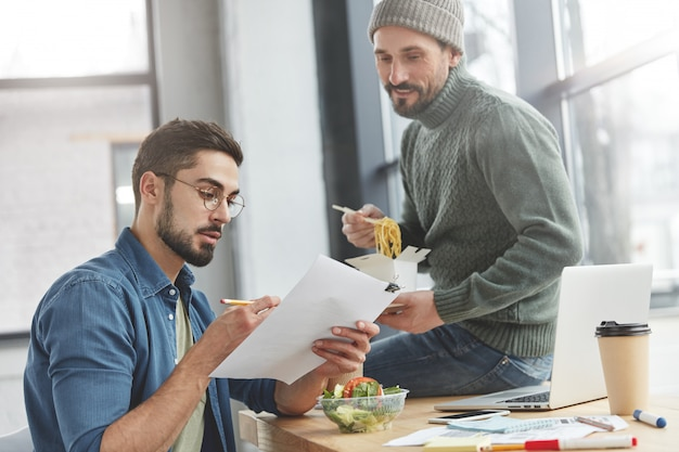 Коллеги-мужчины в офисе с обедом