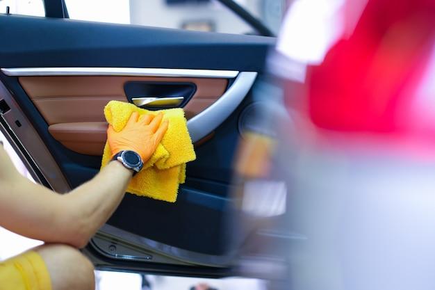 마이크로 화이버가 달린 장갑을 낀 남성 장인은 자동차 근접 촬영의 자동차 손잡이를 닦습니다.