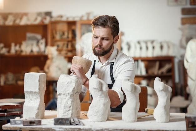 作業服を着た男性職人がクリエイティブスタジオで女性の胴体の石灰岩のコピーを作成し、最初から最後まで製造プロセスを示しています。
