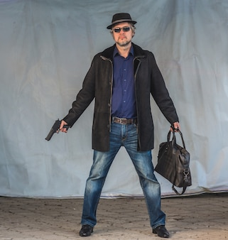 Male criminal with a gun and a bag