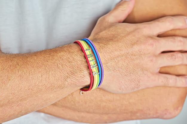 男性は白いtシャツにレインボーブレスレットとテキストプライドで腕を組んだ。 lgbtの愛は自由の概念です