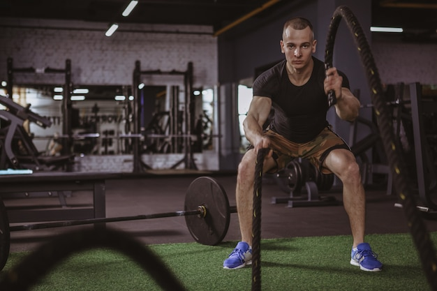 Male crossfit athlete working out with battle ropes at gym