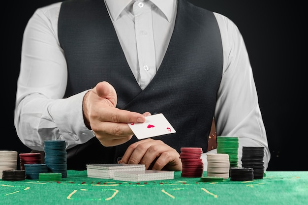 Мужчина крупье в казино за столом вручает крупный план. концепция казино, азартные игры, покер, фишки на зеленом столе казино.