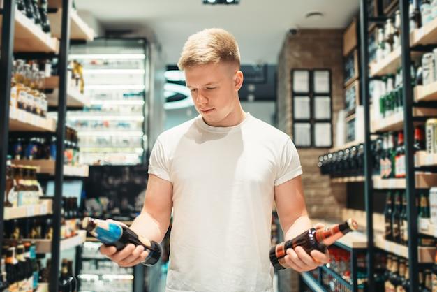 Клиент-мужчина, выбирая пиво в супермаркете. человек делает покупки в разделе алкоголя в продуктовом магазине