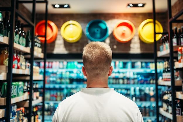 Male customer choosing drinks in supermarket. shopping in food store