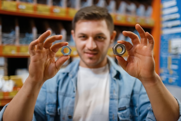 Male customer choosing nuts in hardware store. buyer look at the goods in diy shop, shopping in building supermarket