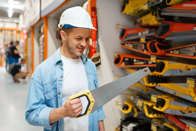 Male customer choosing saw in hardware store