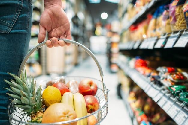 果物のバスケット、スーパーマーケットで食品を選択する人々と男性客の手。食料品店でのショッピング