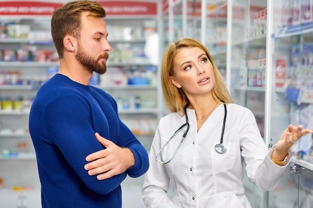 Клиент-мужчина беседует с аптекарем в аптеке