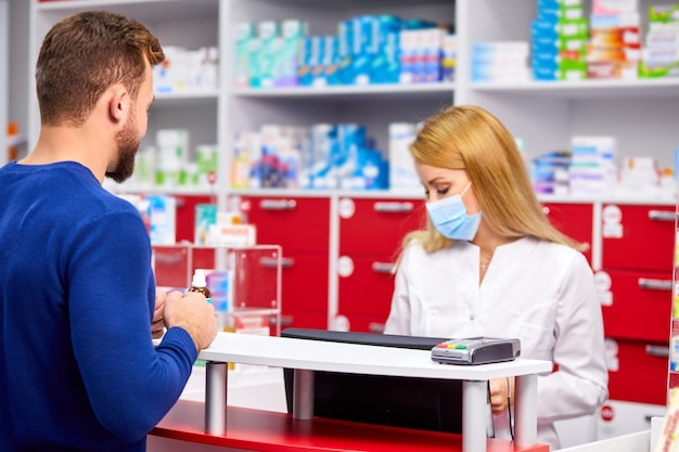 薬局の薬剤師と個別に話し合う男性客