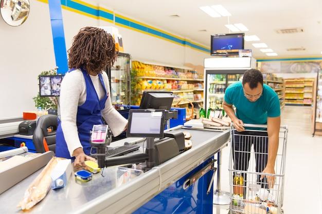 Мужской клиент в повседневной положить продукты из корзины в счетчик