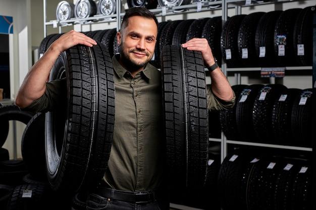 남성 고객은 자동차 수리 차고에서 타이어 구매, 자동차 상점에서 자동차 용 고무를 손에 들고 스탠드에 만족합니다.