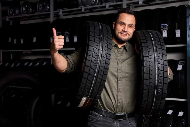 Male customer is satisfied with purchase of tyre in automobile repair garage, stand holding rubber for car in hands,in auto store shop