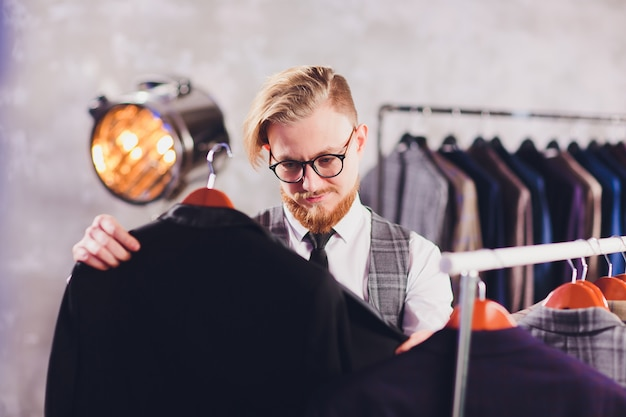 Male customer looking for a jacket in men clothes store.
