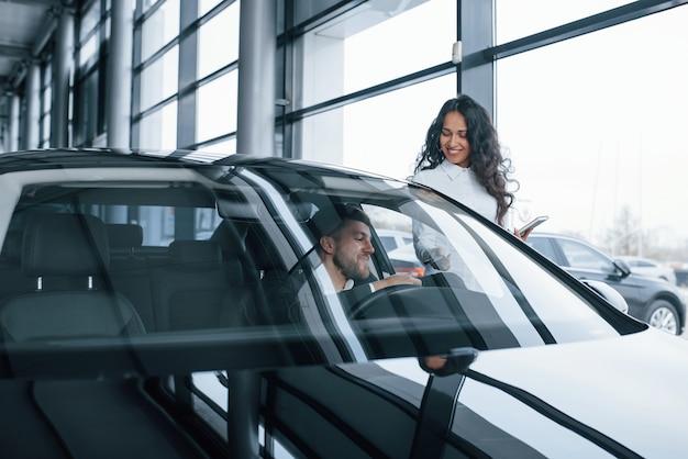 Cliente maschio e donna di affari moderna nel salone dell'automobile