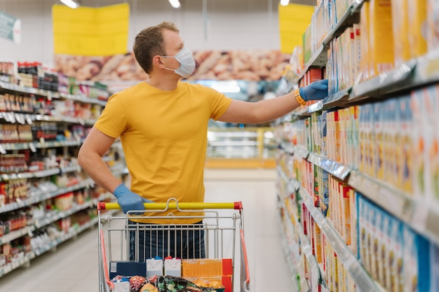 Male customer poses in hypermarket in protective medical mask and rubber gloves, buys necessary products
