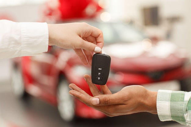 Male customer receiving car keys from salesperson after buying new automobile at the dealership salon
