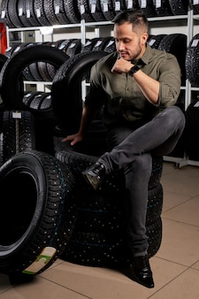 Male customer sit thinking which of tires to buy, caucasian guy in casual wear sits in contemplation in auto service shop, surrounded by black tires for car