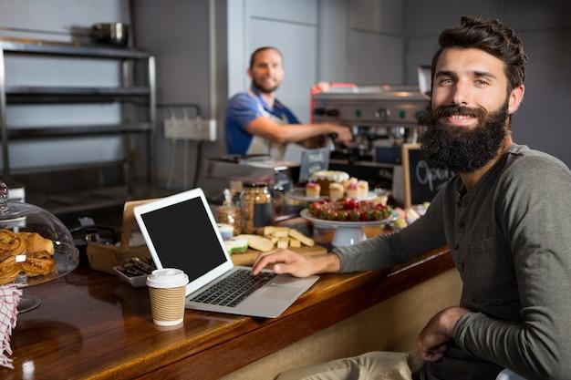 커피 숍 카운터에서 커피를 마시면서 노트북을 사용하는 남성 고객