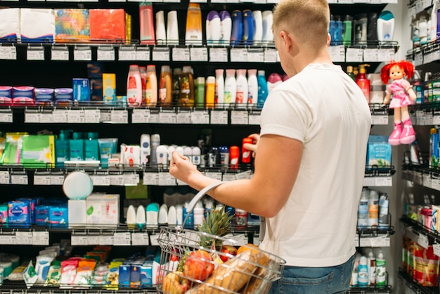 Male customer with basket choosing personal hygiene products in market. shopping in supermarket