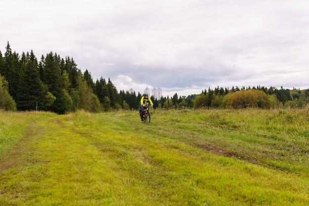 흐린 가을 날 들판을 통해 비포장도로를 달리는 남성 자전거 관광객