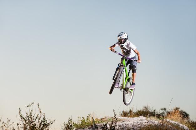 Мужское летание велосипедиста на горном велосипеде над верхней частью горы против голубого неба.
