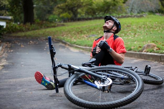 マウンテンバイクから落ちる間に負傷する男性のサイクリスト