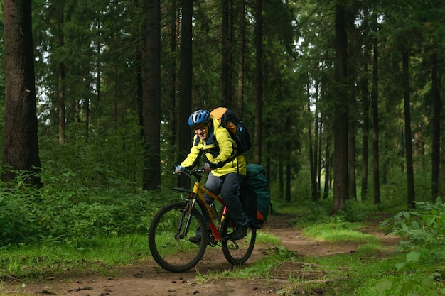 남성 자전거 등산객은 가을 숲의 넓은 흙길을 따라 탄다