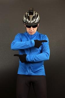 トップフォームの男性サイクリストは、さまざまな方向に彼の手を示しています