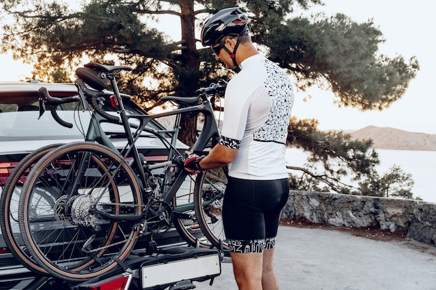 乗車後、クロスオーバー車のラックに自転車を積む男性サイクリスト